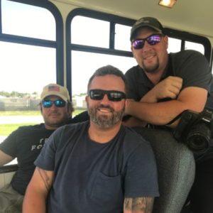 three large white men on a bus
