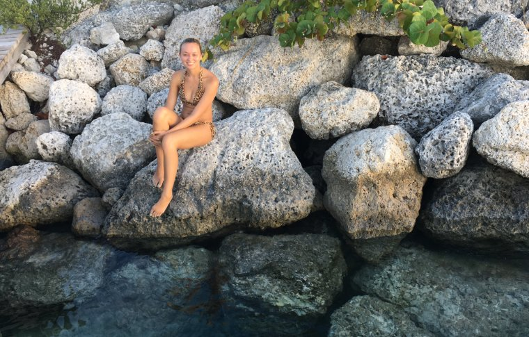 girl perched on rocks above crystal clear water